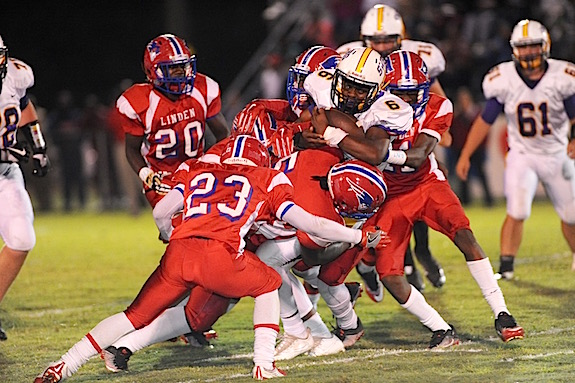 By Johnny Autery A swarming Patriot defense smothers Bulldog RB Shamar Lewis.